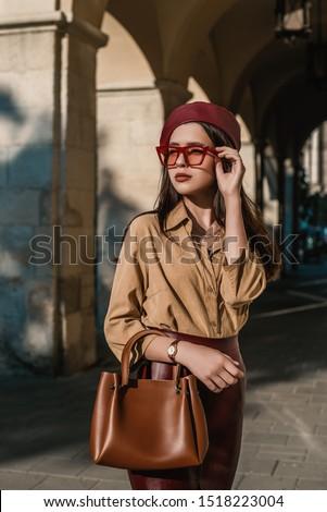 Outdoor, street style, fashion portrait of elegant, luxury woman wearing faux leather dark red beret, sunglasses, beige shirt, wrist watch, holding brown handbag, posing in European city