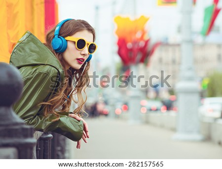 outdoor street style hipster dj woman in yellow sunglasses and blue headphones listen music and smile.