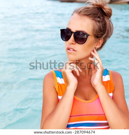 Outdoor summer closeup portrait of pretty young tanned beautiful woman in sunglasses having fun on blue sea background  - Shutterstock ID 287094674