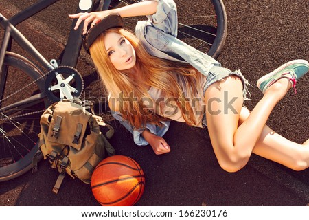 Outdoor summer fashion sensual portrait of beautiful long haired girl lying on the ground with bicycle and basketball ball sport swag style