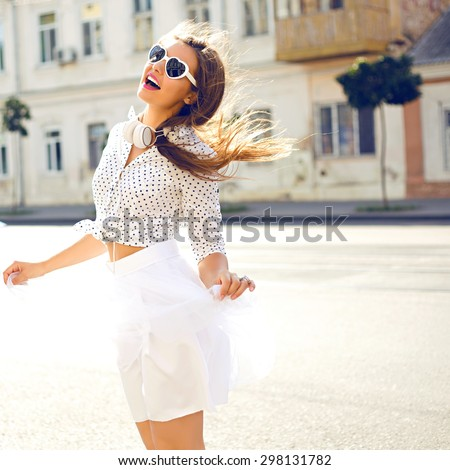 Outdoor summer lifestyle image of young pretty hipster woman having fun, listening music and dancing on the street, city center Europe, cute white vintage outfit and sunglasses, fun ,joy, emotions.