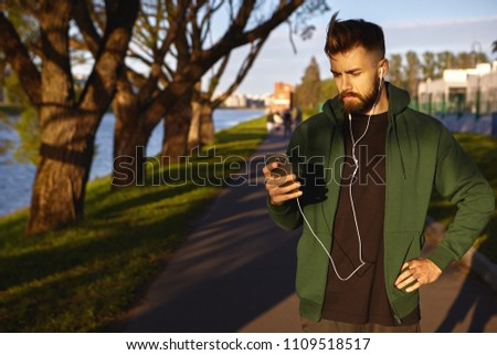 c88f6aa343 Outdoor summer portrait of fashionable young unshaven male athlete wearing  hoodie standing on empty sidewalk during