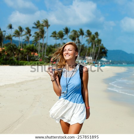 Outdoor summer portrait of young beautiful blonde woman walking on the beach in summer on tropic island vacation having fun near the sea