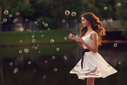 Outdoor summer portrait of young beautiful happy woman making soap bubbles in park or at nature. Joyous happy girl in white dress