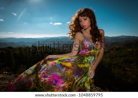 Stock Photo Outdoor summer portrait of young beautiful lady wearing long evening dress in bright colors and colorful print. Pretty girl posing at the mountains background.