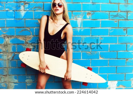 Outdoor summer portrait of young pretty sexy sport style blonde woman in blue pool with big longboard desk and have fun alone in hot weather