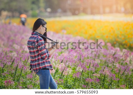 Outdoor summer smiling lifestyle portrait of beautiful young woman having fun in the cosmos flower field with camera travel photo of photographer Making pictures in hipster style
