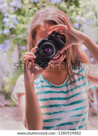 Outdoor summer smiling lifestyle portrait of pretty young woman having fun in evening with camera travel photo of photographer Making pictures