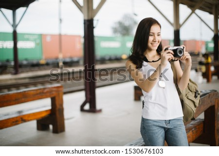 Outdoor summer smiling lifestyle portrait of pretty young woman having fun in the city with camera travel photo of photographer Making pictures