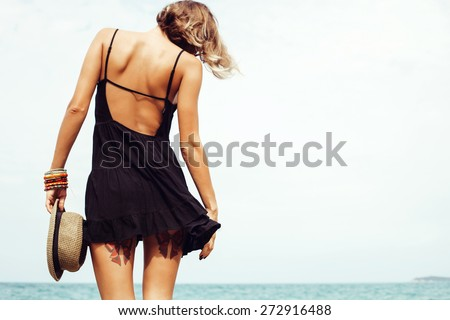 Outdoor summer sunny fashion portrait of pretty young sensual woman posing in black dress on the rocks on the ocean seashore. Outdoors lifestyle portrait