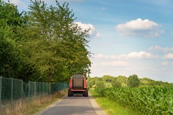 Outdoor sunny view of big truck or tractor run on small road in suburb area surrounded with agricultural field with fresh growing green wheat field in summer season against blue sky in Germany.