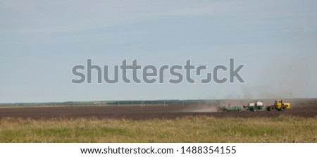 Outdoor sunny view of working combine harvester tractor harvest on golden oat or wheat field during harvesting summer season against deep blue sky