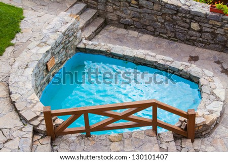 Outdoor swimming pool with blue stone transparent water