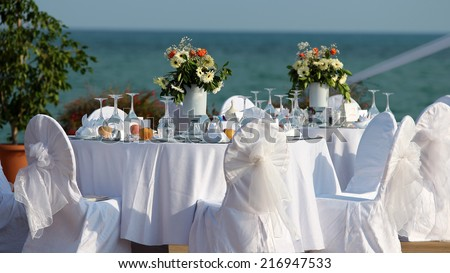 Outdoor Table Setting at Wedding Reception by the Sea. Wedding Chairs and covers at an outdoor wedding. Elegant Outdoor Wedding Table with Sea Views. Table set for an event party or wedding reception.
