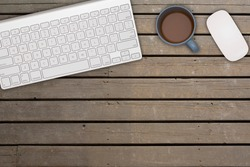 OUTDOOR TABLE WITH KEY COMPUTER KEYBOARD, MOUSE, AND A CUP OF HOT COFFEE. COPY SPACE