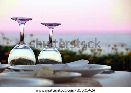 outdoor table with wine glasses over magenta sky