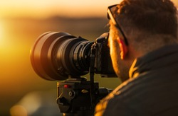 Outdoor Telephoto Photography. Caucasian Photographer in His 20s with Large Telephoto Lens Taking Pictures During Scenic Sunset Using Camera Tripod.