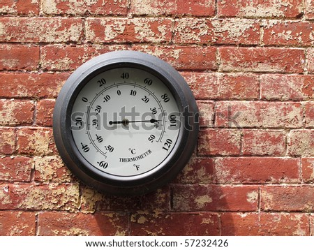 outdoor thermometer on brick wall