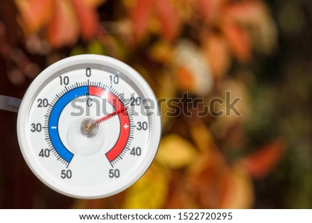 Outdoor thermometer with celsius scale showing warm temperature, blurred autumn leaves seen in background - hot indian summer or global warming concept #1522720295