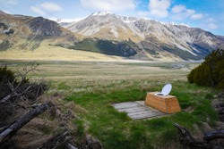 Outdoor toilet with an open toilet seat in the middle of wilderness located in a valley surrounded with many mountains and with an epic view in New Zealand
