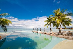 Outdoor tourism landscape. Luxurious beach resort with swimming pool and beach chairs or loungers umbrellas with palm trees and blue sky, sea horizon. Summer island relax travel and idyllic vacation
