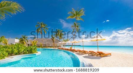 Outdoor tourism landscape. Luxurious beach resort with swimming pool and beach chairs or loungers under umbrellas with palm trees and blue sky. Summer island travel and vacation background concept