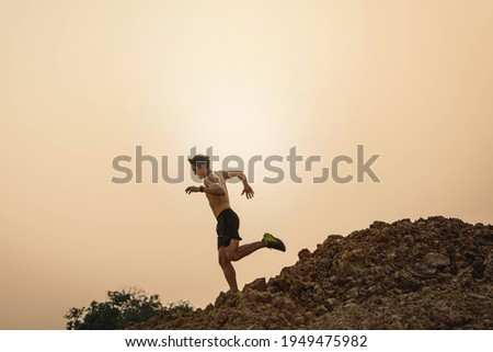 Outdoor trail running in early sunrise concept for exercising, fitness and healthy lifestyle. Young people running on country trail path. Athletes Sport Man Trail Running in the Forest .