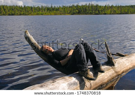 Outdoor travel. Happy young woman lies on a log on the lake. Keret river, Republic of Karelia, Russia. Stock fotó ©