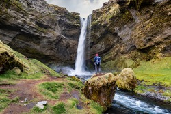 outdoor travel, tourist man standing on a rock and looking at Kvernufoss waterfall landscape in Iceland