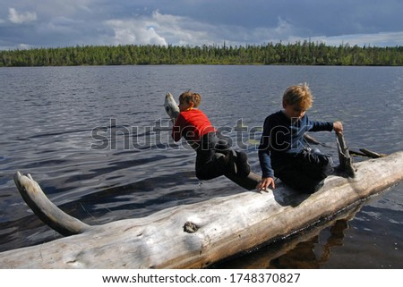 Outdoor travel. Two boys hanging out on a log on the lake. Keret river, Republic of Karelia, Russia. Stock fotó ©
