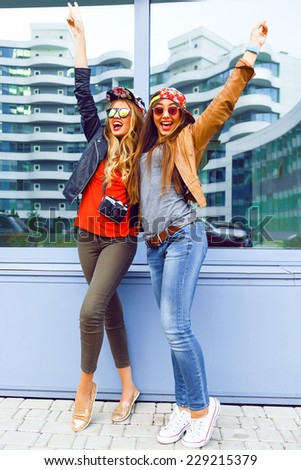 Outdoor urban lifestyle portrait of two pretty girls best friends screaming laughing and put their hands to the air. wearing casual bright clothes hats and sunglasses, happy mood emotions.
