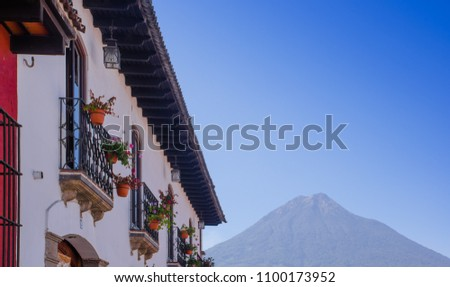 Outdoor view of balcony with some flowers in a pot of ancient building in the main street of Antigua city with agua volcano in the background during sunrise