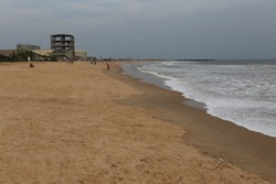 Outdoor view of the beach of cotonou city, benin, west Africa. Seascape with buildings under construction near the sand. White waves on the atlantic sea. African capital.