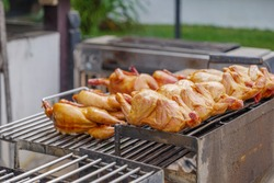 Outdoor view, Row of Thai style Whole Grilled chickens on open gridiron over burning charcoal on grilling machine.