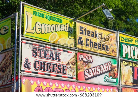 Outdoor Vinyl Banner Selling Delicious Hot Carnival Foods, Conveying the Concept of Advertising, Exterior, Afternoon Sunlight, Medium Shot, Low Angle.