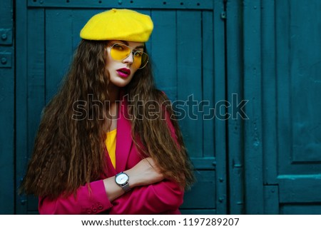Outdoor waist up fashion portrait of young beautiful fashionable woman wearing stylish yellow beret, trendy sunglasses, pink blazer, wrist watch, posing near blue doors. Copy, empty space for text