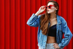 Outdoor waist up portrait of young beautiful fashionable girl posing in street. Model wearing stylish jeans denim jacket, sunglasses. Red background. Female fashion concept. Copy, empty space for text
