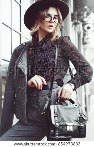 Outdoor waist up portrait of young beautiful girl, businesswoman posing in street. Model wearing stylish clothes, trendy glasses, hat, holding bag, briefcase. City lifestyle. Female fashion concept #654973633