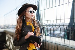 Outdoor waist up portrait of young beautiful woman with long hair, looking aside. Model wearing stylish hat,  white round sunglasses, clothes, holding small bag. City lifestyle. Female fashion concept