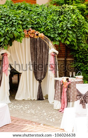 Outdoor wedding arch with table under grapevine
