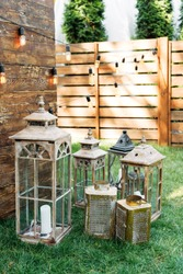 Outdoor wedding ceremony. Oldfashion wooden lanterns in rustic style on the grass