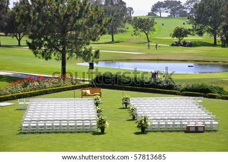 stock photo Outdoor wedding reception venue set up with white chairs and