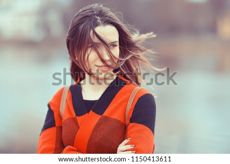 Outdoor wind hair fall / autumn portrait adult girl model woman with long hair in a windy day in the park