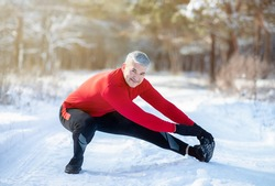 Outdoor winter activities concept. Joyful senior man stretching his legs before jogging at snowy park on cold day. Athletic mature guy doing warmup exercises, working out outside in frosty weather