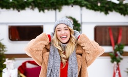 Outdoor Winter Portrait Of Happy Beautiful Young Blonde Woman Posing Near Campervan, Cheerful Millennial Female Laughing At Camera, Enjoying Spending Christmas Holidays At Campsite, Closeup