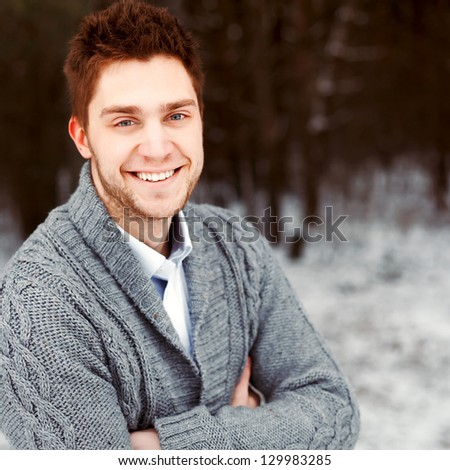 Outdoor winter portrait of happy young smiling man - stock photo