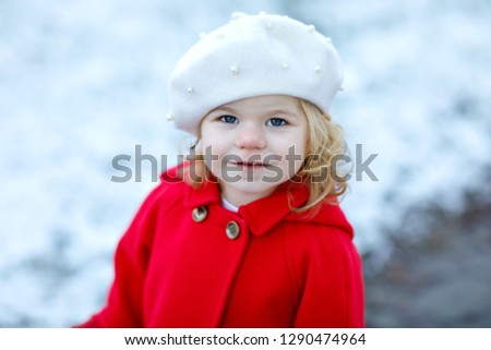 c900e13b422f5 Outdoor winter portrait of little cute toddler girl in red coat and white  fashion hat barret