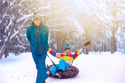 Outdoor Wintersport Activities. Happy Caucasian Couple Having Tube Activities In Winter Forest While Man Hauling Girl by Rope With Smile. Horizontal Image