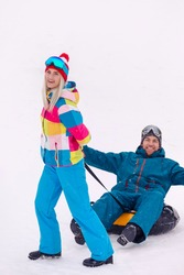 Outdoor Wintersport Activities. Happy Caucasian Couple Having Tube Activities In Winter Forest While Girl Hauling Man by Rope With Smile. Vertical Image