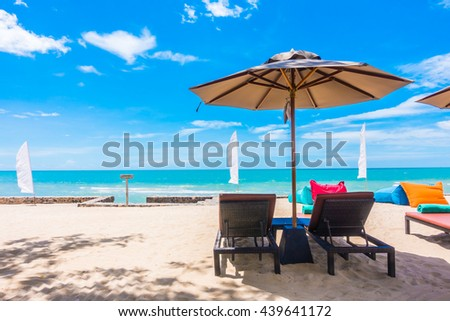 Outdoor with umbrella and chair on beautiful tropical beach and sea and blue sky background #439641172